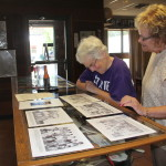 Linda Jones and Kathy Coup enjoy old class pictures.